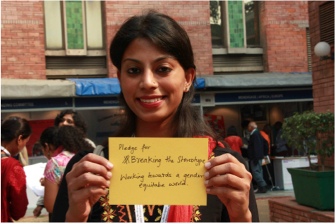 Meera Vijayann holds up a pledge at the symposium